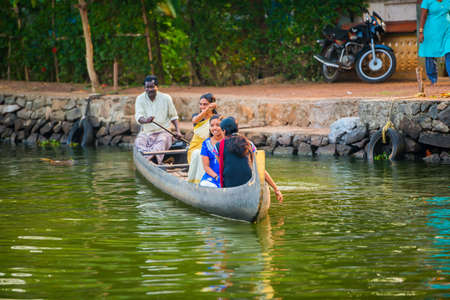 alappuzha: ALLEPPEY, INDIA - FEBRUARY 23: An unidentified man and women are floating in a traditional boat. India, Kerala, Alleppey (Alappuzha). February 23, 2013