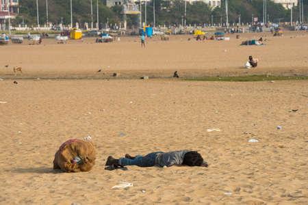 underprivileged: CHENNAI, INDIA - 10 febbraio: Un giovane uomo non identificato dorme sulla sabbia vicino alla Marina Beach il 10 febbraio 2013, Chennai, India.
