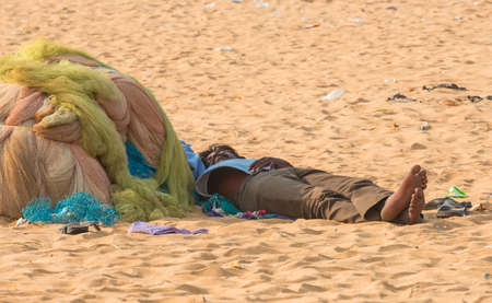 underprivileged: CHENNAI, INDIA - FEBRUARY 10: An unidentified man sleeps on the sand near the Marina Beach on February 10, 2013 in Chennai, India.