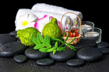 bergamot fruit, verse munt, rozemarijn, kaarsen, handdoeken, bloemen en flessen essentiële olie op zen stenen