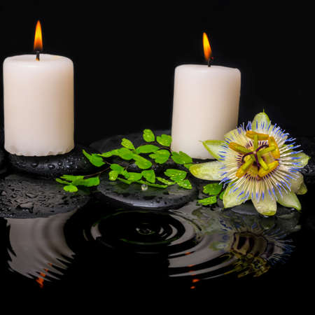 reflection of life: spa still life of passiflora flower, green leaf fern with drop and candles on zen stones in ripple reflection water, closeup Stock Photo