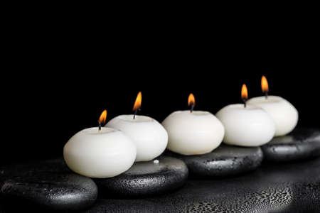 spa concept of white candles on zen stones with water dew black background, closeup