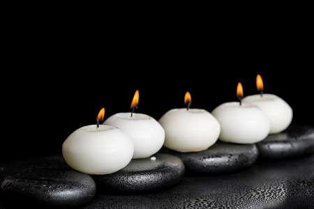 spa concept van witte kaarsen op zen stenen met water dauw zwarte achtergrond, close-up