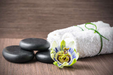 passiflora: beautiful spa concept of passiflora flower, black zen stones and white towels on wooden background, closeup Stock Photo