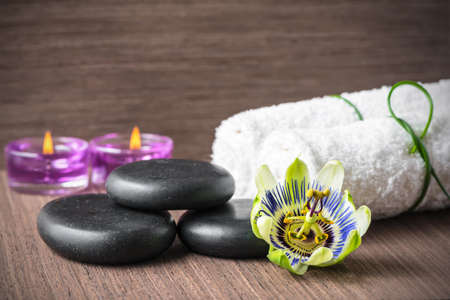 purple floral: beautiful spa concept of passiflora flower, black zen stones, purple candles and white towels on wooden background, closeup Stock Photo