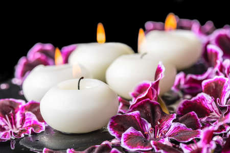 reflection of life: beautiful spa still life of blooming dark purple geranium flower, beads and candles in reflection water, closeup
