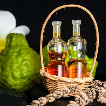 Aromatic spa concept of bottles essential oil in basket, flower, bergamot, candles and black zen basalt stones with dew 免版税图像