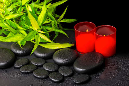 spa concept of twigs bamboo with dew and red candles on zen basalt stones, closeup photo