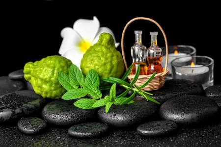 Aromatic spa of bottles essential oil in basket, fresh mint, rosemary, bergamot fruits, flower and candles on black zen stones