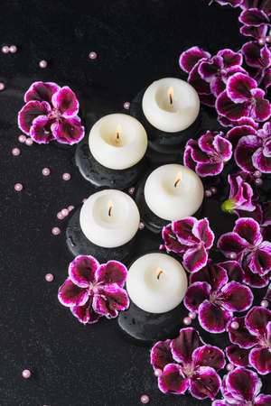 reflection of life: beautiful spa still life of geranium flower, beads and candles in reflection water, closeup Stock Photo