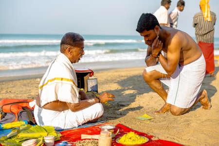 indian ocean: Varkala, India - February 22, 2013: Hindu Brahmin with religious attributes providing ceremony and are blessing pilgrim in the morning. Varkala beach, Kerala, India