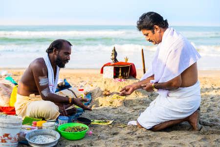 providing: Varkala, India - February 22, 2013: Hindu Brahmin with religious attributes providing ceremony and are blessing pilgrim. Varkala beach, Kerala, India