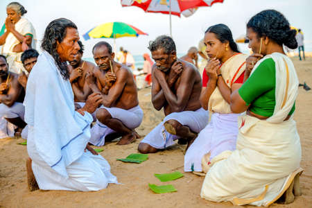 providing: Varkala, India - February 22, 2013: Hindu Brahmin with religious attributes providing ceremony and are blessing pilgrims. Varkala beach, Kerala, India Editorial