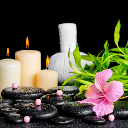 massage stones: spa composition of hibiscus flower, bamboo, thai herbal compress ball, beads and candles on zen basalt stones with drops, closeup Stock Photo