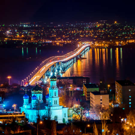 urban decline: beautiful landscape of evening city Saratov with church and bridge through the Volga River, Russia