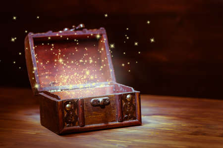 treasure chest: beautiful background of mystery chest with light miracle on wooden background with place for text, closeup Stock Photo