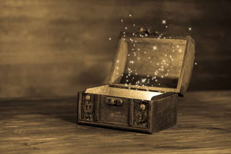 mysteries: beautiful retro chest with sparkles on wooden background with place for text, closeup, sepia style