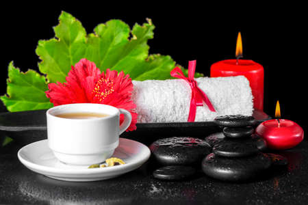 spa flower: beautiful spa concept of red hibiscus flower with dew, candles, green leaf, cup of tea and rolled towel on zen stones, closeup