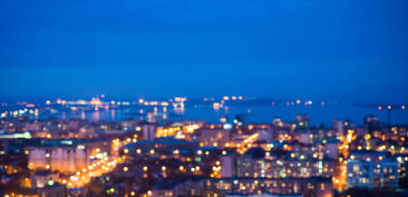 urban decline: defocused abstract city lights in the twilight with river, reflection and horizon, bokeh background, panorama Stock Photo