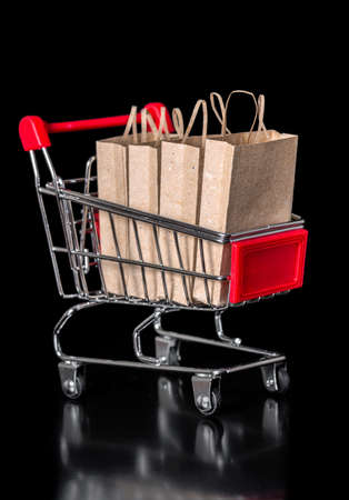chrome cart: concept of sale shopping cart with paper bags is isolated on black background, closeup