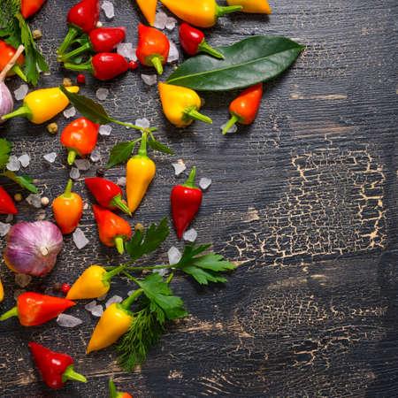 de haut en bas de jaune, rouge hot chili peppers, sel de mer, verdure, poivre noir et de l'ail sur fond noir fissures, fermer