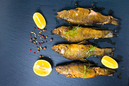 tench: top view of fried tench fish served with aromatic rosemary, lemon and dry peppers on slate background, close up Stock Photo
