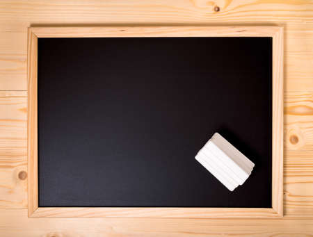 white chalks: top down empty blank school black board with white chalks on wooden background, close up