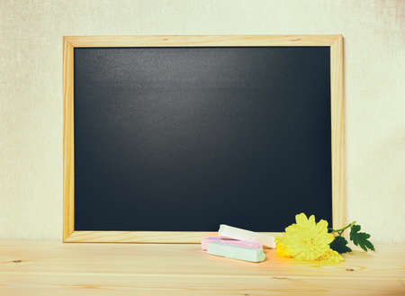 white chalks: empty blank school black board with white chalks and chrysanthemum flower on wooden background, toned instagtam style, close up Stock Photo