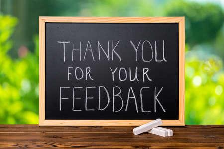 handgeschreven tekst dank u voor uw feedback in schoolbord op groen licht achtergrond en rustieke houten bord wordt geschreven, close-up