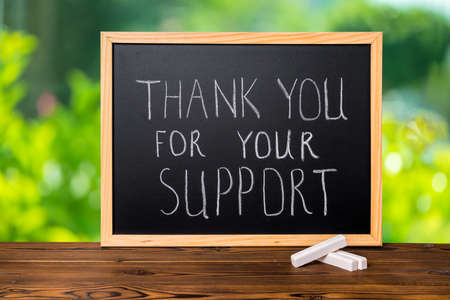 handwriting text thank you for your support is written in chalkboard on green light background and rustic wooden board, close up Stock Photo