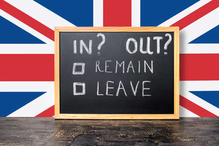 skepticism: Brexit UK EU referendum concept with flag and handwriting text in, out, leave, remain is written in chalkboard, close up