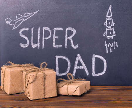 super dad: concept of Fathers Day with handwritten text Super Dad and pictured airplane, rocket with gift boxes on blackboard over wooden background