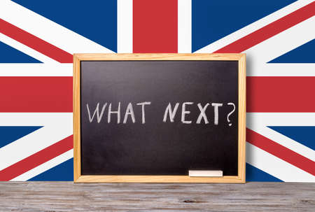separatism: Brexit UK EU referendum concept for out of Great Britain from rest European union and handwriting text what next written in chalkboard with chalk on flag, close up