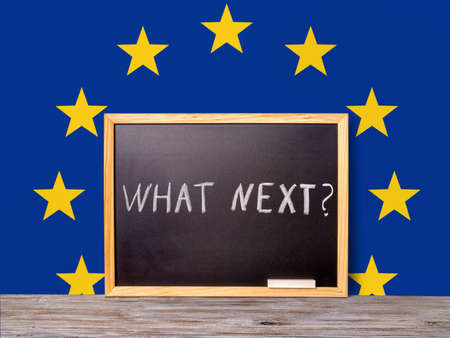 skepticism: Brexit UK EU referendum concept for out of Great Britain from rest European union and handwriting text what next written in chalkboard on flag background, close up