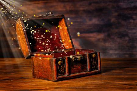 schöne Grußkarte von mit Wunder magisches Licht und goldenen Sonne Jahrgang Brust Schatz geöffnet Strahlen auf Holzuntergrund, Kunst-Design mit Kopie Raum, close up