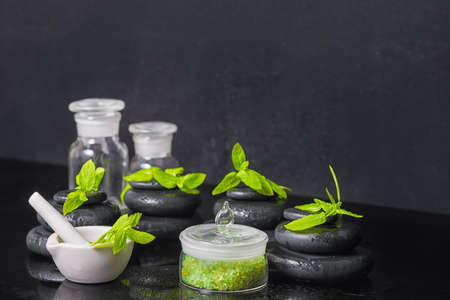 mortar and pestle: spa background of pyramid zen basalt stones with water drops, mint, sea salt, mortar, pestle and bottles of tincture on black, close up Stock Photo
