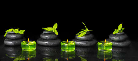 spa background of pyramid zen basalt stones with water drops, mint and green candles on black, close up 免版税图像