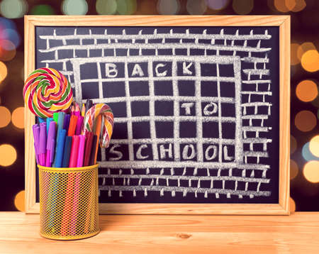 pen holder: humorous concept of hate school as prison with text back to school is written in chalkboard, pen holder, peppermint candy on wooden table over blur background, close up Stock Photo