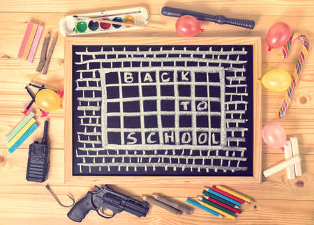 top view humorous concept of hate school as prison with text back to school is written in chalkboard, chalks, toys and colorful pencils on wooden table, close up