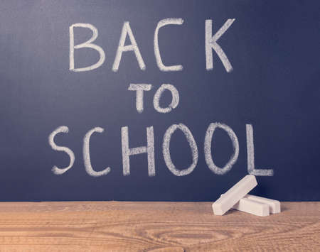 white chalks: simple background of education with text back to school is written in chalkboard and white chalks, toned style, close up