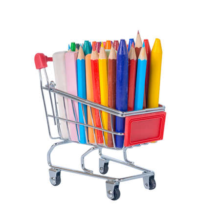 pushcart: education concept with chrome shopping cart, pens, crayons, colorful chalks is isolated on white background, close up