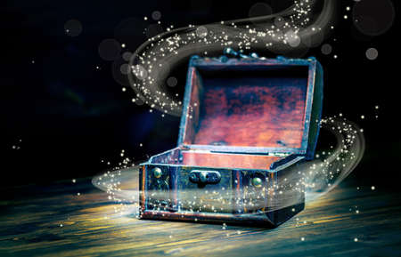 beautiful concept greeting card of opened vintage chest treasure with miracle magic light on wooden background, art design with copy space, close up