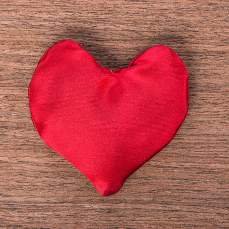 sewn: one red homemade sewn heart on wooden background, concept Valentines day, greeting card, close up