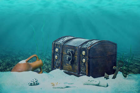submerging: beautiful opened empty old wooden treasure chest submerged underwater world with anchor, amphora and light rays, close up