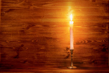 the art of divination: burning old candle with vintage brass candlestick on wooden background, natural light, close up