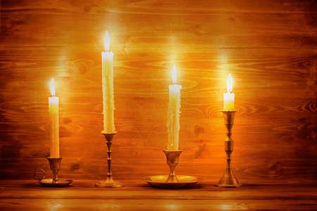 shabat: hermosas velas con cuatro diferentes candelabros de época sobre fondo de madera, de cerca Foto de archivo