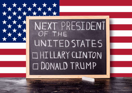 senate elections: American election concept with flag and handwriting text next president of United States Donald Trump Hillary Clinton written in chalkboard background, close up Stock Photo