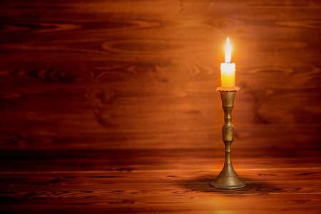 brandende kaars oude met vintage koperen kandelaar op houten achtergrond in minimalistisch interieur, close-up