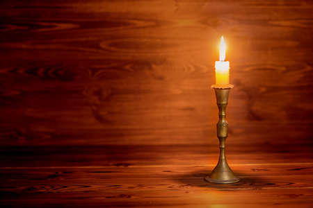 burning old candle with vintage brass candlestick on wooden background in minimalist room interior, close up