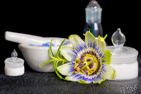 beautiful spa setting of blue passiflora flower, cosmetic salt mortar and fragrance bottle on zen stones with dew, close up Stock Photo